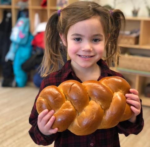 A young girl holds a loaf of challah