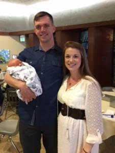 Proud parents stand holding their new baby at a birth celebration at Temple Beth Shalom.