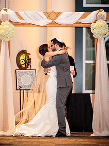 Rabbi Tamar stands with a couple under the chuppah during a wedding at Temple Beth Shalom.