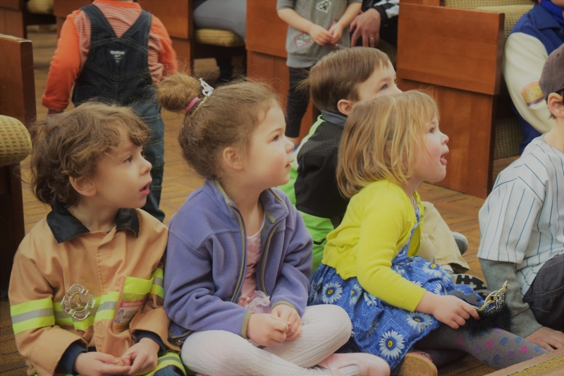 Children in costumes listening to a story, intently paying attention