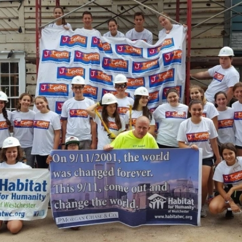 teens with hardhats pose with 9/11 banner for Habitat for Humanity
