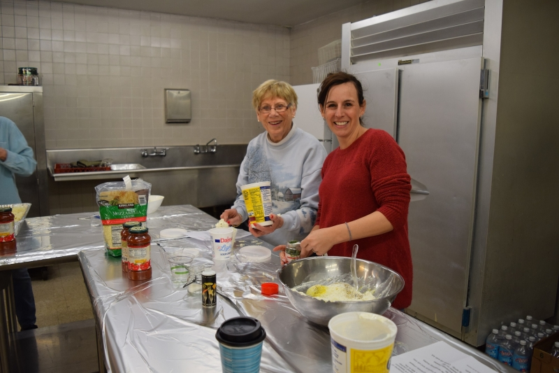 two female congregants make ziti for local soup kitchen