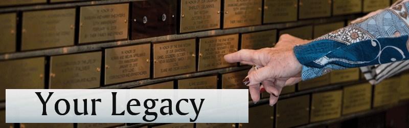 An older woman's hand pointing to a memorial plaque on Congregation B'nai Amoona's Memorial Wall. The Memorial Plaques are two inches by four inches and plated in gold with engraved letters spelling out English and Hebrew names of people who have passed away.