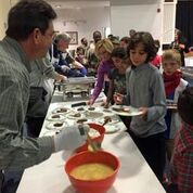 Men's club members serve latkes to Mosad Shalom students to celebrate Chanukah