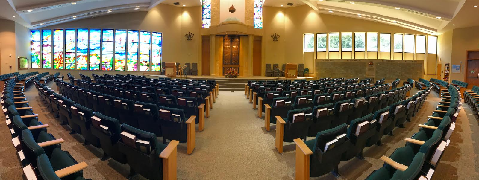 An image of the CBI Sanctuary, showing the Windows of Wonder and the bimah. A beautiful display of white flowers is arrayed in front of the central podium on the bimah. The room is full of light.