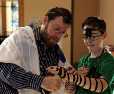 Cantor Jonathan Schultz helps a happy young congregant wrap his tefillin.