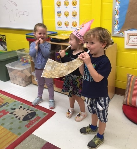 Children blowing on their toy shofars