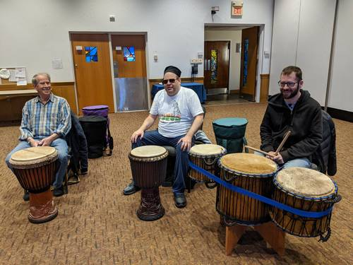 Three members of the drum circle, showing off some special rare African drums
