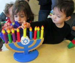 two little kids playing with wooden menorah