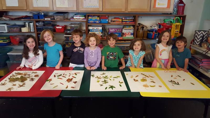 Eight Smiling ECC students display leaf hunt findings