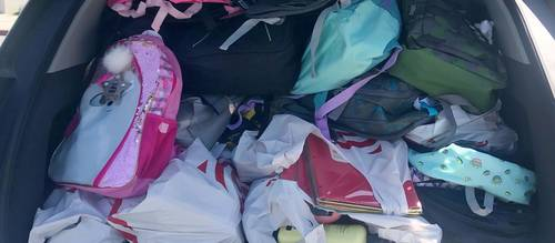 Car trunk filled with many backpacks and school supplies.
