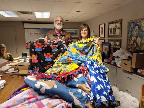 Two Temple members holding up donated blankets for Share the Warmth