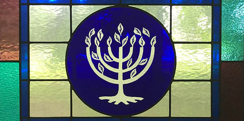 Stained glass window at Temple Israel with menorah from Temple Israel logo.