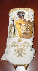 "Torah from Beth Israel, Stratford, ON. The Torah is dressed in an embroidered cloth cover, breastplate reads ""It is a Tree of Life to those who hold fast to it."""