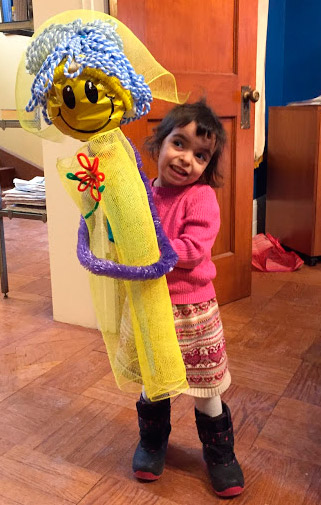 Little girl playing with homemade doll as large as she is.