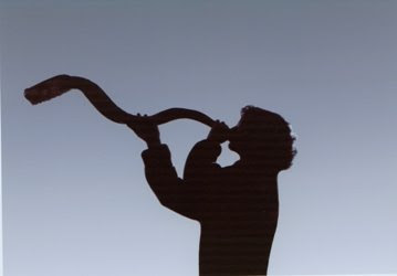 silhouette of woman sounding shofar