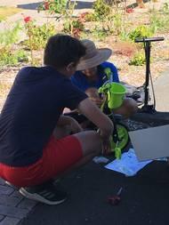 Volunteers work on little trikes for PHFS children.