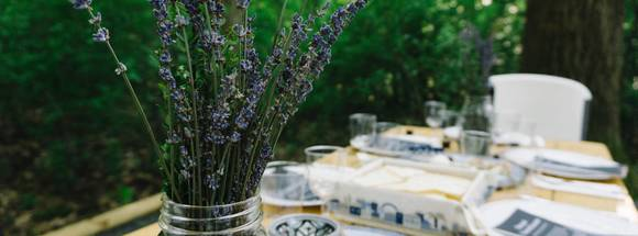 A vase of lavender on a seder table outdoors.